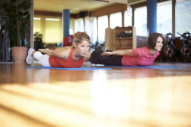 Woman exercising with coach in fitness studio - MAOF000011