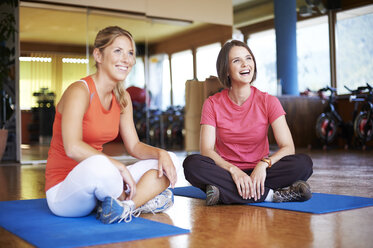 Coach and client sitting cross-legged on floor in fitness studio - MAOF000080