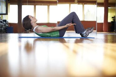 Woman in fitness studio doing abdominal trainiing - MAOF000012