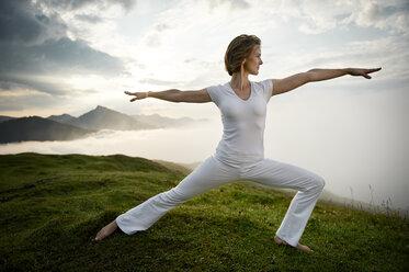 Austria.Kranzhorn, Mid adult woman practising yoga on mountain top - MAOF000021