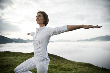 Austria.Kranzhorn, Mid adult woman practising yoga on mountain top - MAOF000028