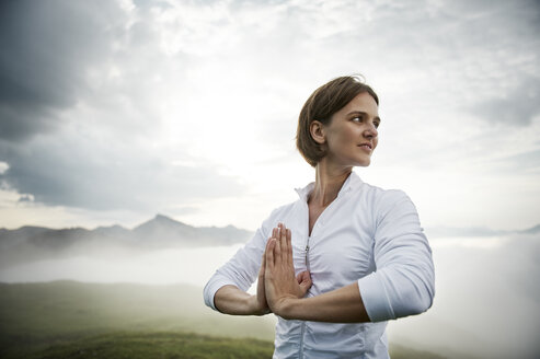 Austria.Kranzhorn, Mid adult woman practising yoga on mountain top - MAOF000029