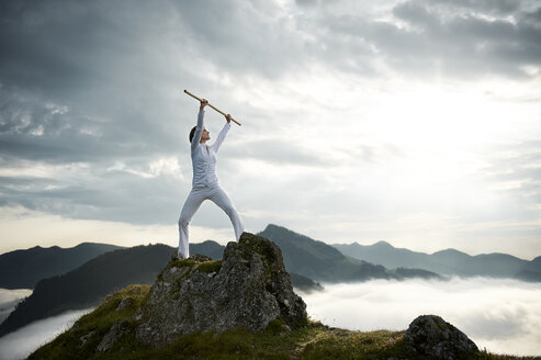 Austria, Kranzhorn, Mid adult woman exercising stick fighting on mountain top - MAOF000031