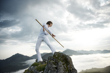 Austria, Kranzhorn, Mid adult woman exercising stick fighting on mountain top - MAOF000032
