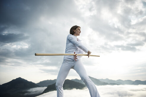 Austria, Kranzhorn, Mid adult woman exercising stick fighting on mountain top - MAOF000033