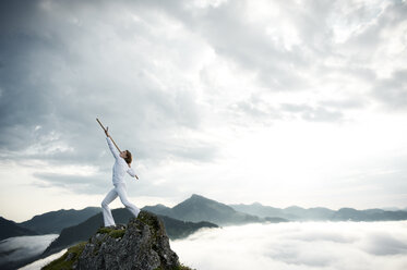 Austria, Kranzhorn, Mid adult woman exercising stick fighting on mountain top - MAOF000034
