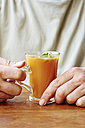 Man with sweet potato, carrot and apple soup in a glass - HAWF000720