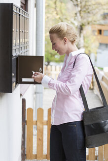Woman standing in front of mailbox watching letter - NNF000200