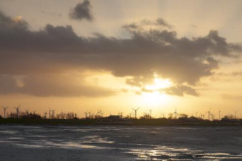Germany, Bensersiel, coastal landscape with wind turbines at sunset - WIF001573