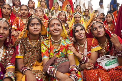 India, Rajasthan, Pushkar, young women at camel market Pushkar Mela wearing typical traditional clothing - PC000082