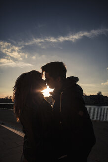 Germany, Berlin, teenage couple kissing on a promenade along a lake - MMFF000526