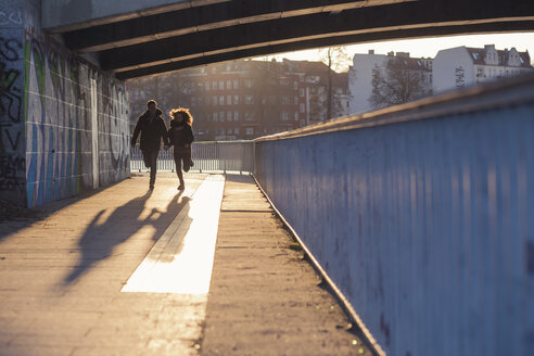 Germany, Berlin, teenage couple running under a bridge at evening sunlight - MMFF000528
