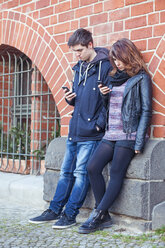 Teenage couple standing in front of a brick house using smartphones - MMFF000513