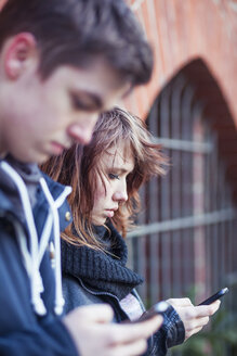 Teenage girl with smartphone, boy blurred in the foreground - MMFF000510
