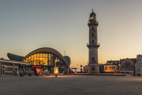 Germany, Warnemuende, restaurant Teepott and lighthouse at sunrise - MELF000053