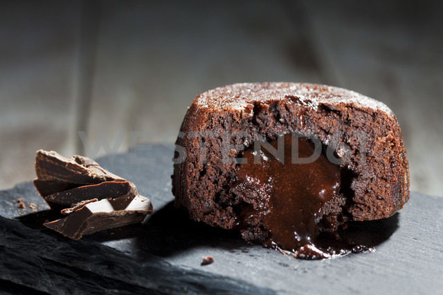 Sliced small chocolate tart with melted chocolate filling on slate - CSF024957
