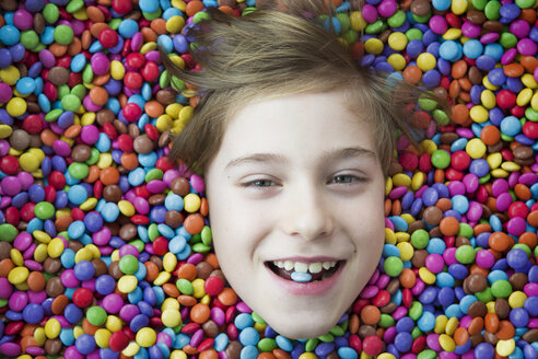 Boy bathing in chocolate buttons - JTLF000065
