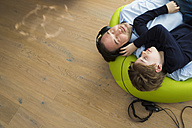 Father and son lying on bean bag in living room listening music - JTLF000069