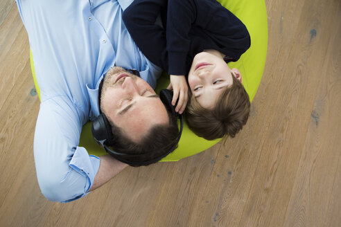 Father and son lying on bean bag in living room listening music - JTLF000071