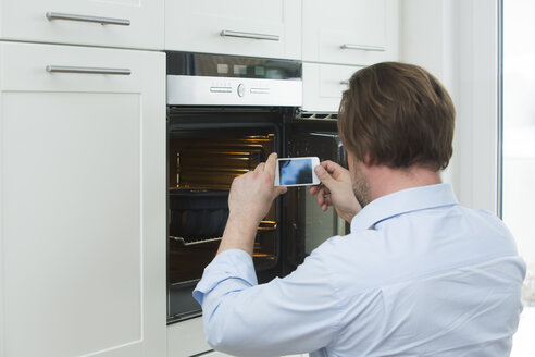 Man photographing cake in the oven with smartphone - JTLF000076