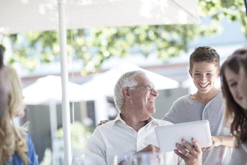 Grandfather and grandson using digital laptop at restaurant - ZEF004082