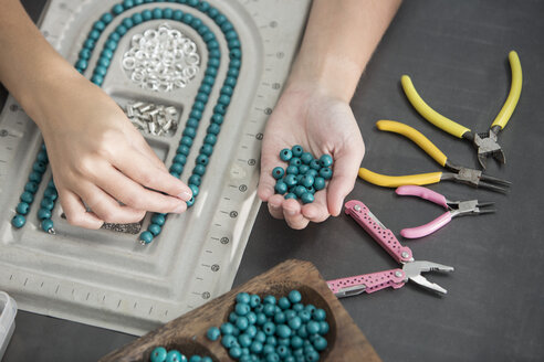 Close-up of woman working with beads to create a necklace - ZEF003639