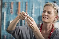Woman working with pliers to create a bead necklace - ZEF003652