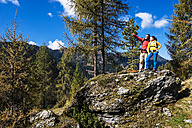Austria, Altenmarkt-Zauchensee, young couple standing on a rock looking at view - HHF005157
