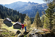 Austria, Altenmarkt-Zauchensee, young couple standing on a rock looking at view - HHF005165