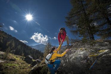 Austria, Altenmarkt-Zauchensee, young couple climbing on a rock - HHF005166
