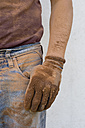 Close-up of man with dirty working glove - CRF002657