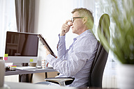 Businessman working with digital tablet at home office - SEGF000268