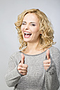 Portrait of happy blond woman with thumbs up - MAEF009925