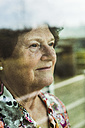 Portrait of senior woman looking through window - UUF003572