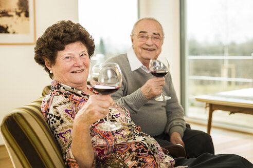 Senior couple relaxing with glasses of red wine - UUF003583