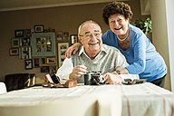 Happy senior couple with old camera at home - UUF003588