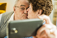 Senior couple taking a selfie with smartphone at home - UUF003593