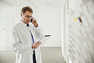 Mature man in lab coat on phone looking at digital tablet - MFF001522