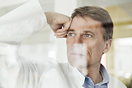 Portrait of mature man in lab coat behind glass pane - MFF001533