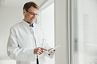 Smiling mature man in lab coat using digital tablet at the window - MFF001538