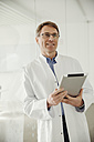 Smiling mature man in lab coat holding digital tablet - MFF001543