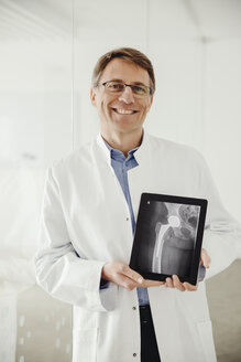Mature man in lab coat presenting an x-ray scan on his digital tablet - MFF001546