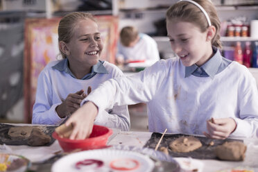 Two girls working on modeling clay in art class at school - ZEF005967