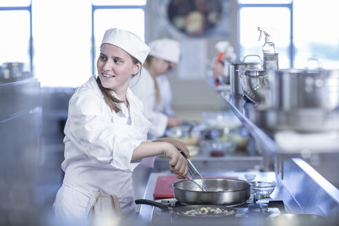 Teenage girl cooking in canteen kitchen - ZEF005946