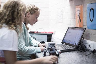 Two schoolgirls with laptop in robotics class - ZEF006092