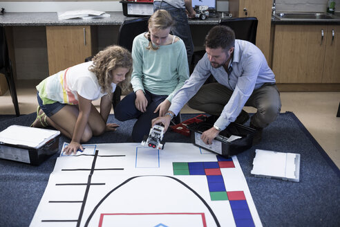 Teacher with schoolgirls on test track in robotics class - ZEF006095
