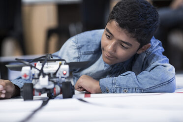 Schoolboy in robotics class testing vehicle on test track - ZEF006097