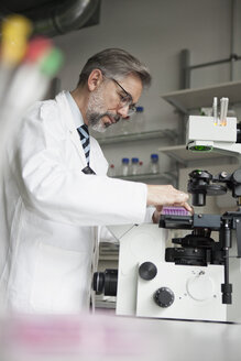Scientist in laboratory working at microscope - RBF002530