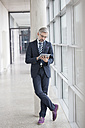 Businessman leaning against column using digital tablet - RBF002550