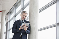 Businessman leaning against column using digital tablet - RBF002551